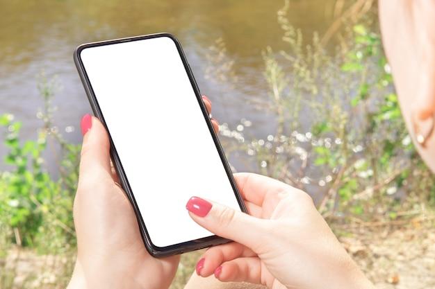 Telefono mockup. tocco della mano del primo piano sullo schermo nero in bianco del telefono mobile all'aperto sulla natura sfocata