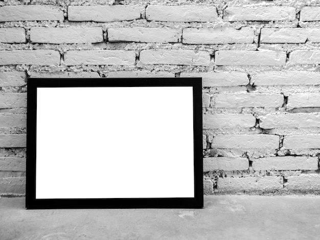 Cornice per foto mockup. immagine quadrata bianca con mockup di cornice nera su ripiano in cemento e sfondo di muro di mattoni bianchi con spazio di copia.