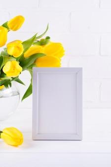 Il modello della cornice ha decorato i fiori gialli del tulipano in vaso su fondo bianco con spazio pulito per testo e progettazione