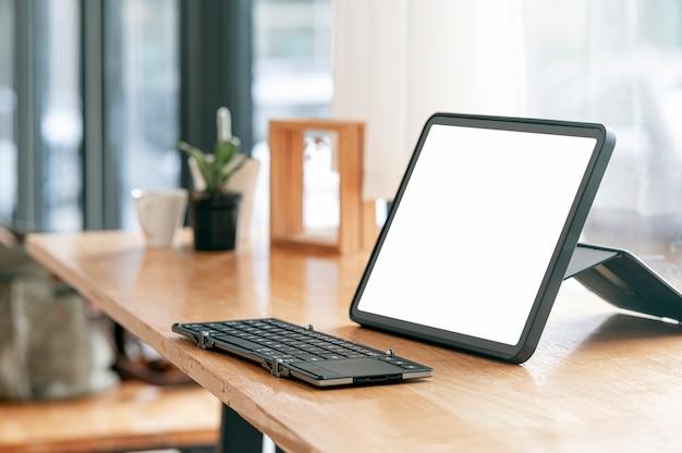 Compressa e tastiera portatili dello schermo in bianco del modello sulla tavola di legno con lo spazio della copia.