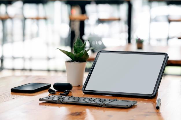 Tablet portatile mockup con tastiera e gadget sul tavolo di legno nella stanza dell'ufficio.