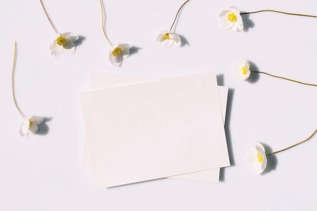 Mockup poster flyer per invito alla presentazione carta vuota e fiori bianchi con ombre dure su uno sfondo grigio vista dall'alto