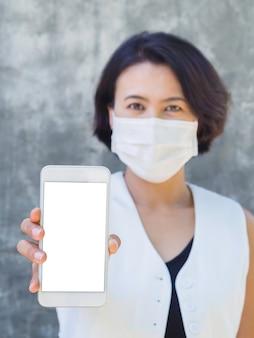 Schermata mockup sullo schermo dello smartphone. donna asiatica che indossa camicia bianca e maschera protettiva che mostra uno spazio vuoto bianco sul telefono, stile verticale.