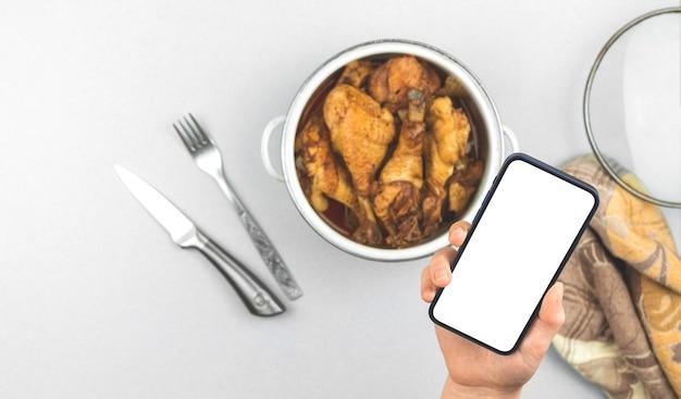 Schermata mockup con pollo fritto casalingo arrosto in una casseruola, menu di cibo sano per foto concetto ristorante, schermo bianco, foto spazio copia