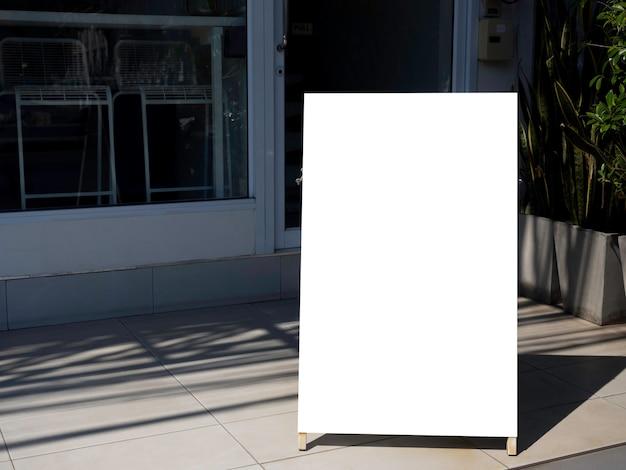 Mockup segnaletica all'aperto a terra di fronte al ristorante o al bar. cornice quadrata vuota bianca per informazioni sullo sfondo di un edificio moderno.