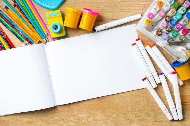 Mockup sketchbook carta vuota sul tavolo. pennarelli e matite sono sparsi nelle vicinanze. vista dall'alto.