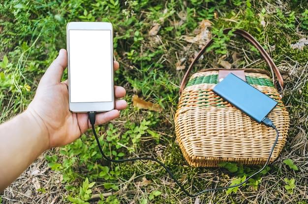 Mockup di uno smartphone nella mano di un ragazzo. sullo sfondo il power bank e la gorzina a terra.