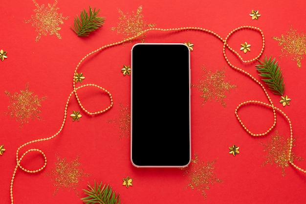 Mockup di smartphone con schermo nero su sfondo rosso di natale decorato