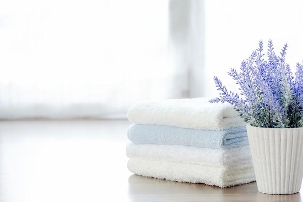 Pila di modello di asciugamani e houseplant sul tavolo bianco con spazio di copia.