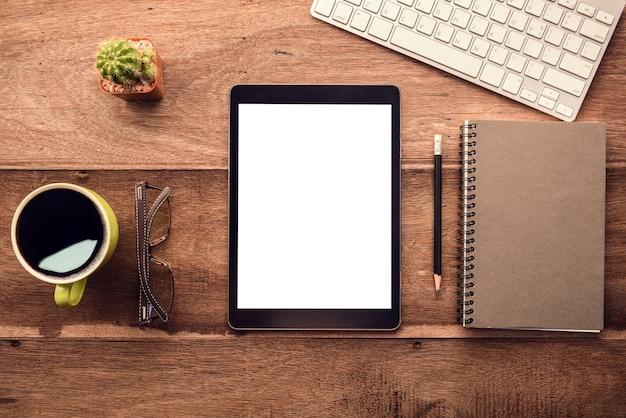 Tablet mockup simile allo stile ipad su scrivania in legno bianco display.keyboard e roba per ufficio.