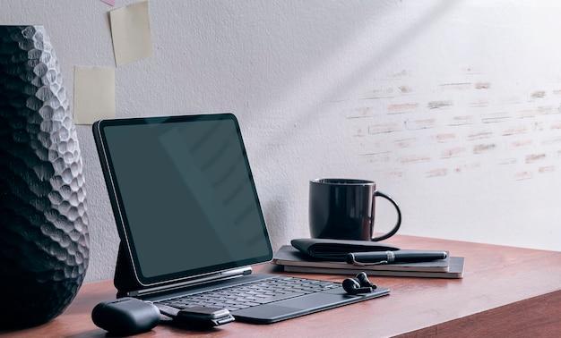 Tablet mockup con tastiera magica e gadget sul tavolo di legno.