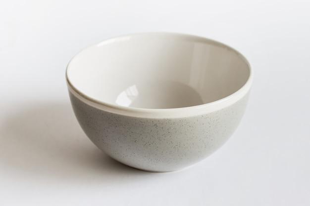 Modello di mockup di un piatto unico in porcellana con colore grigio punteggiato su superficie bianca.
