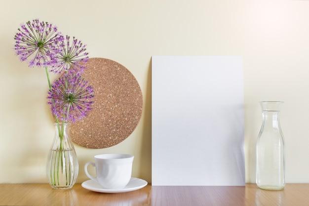 Modello mockup con foglio di carta a4, tazza di porcellana, fiori di aglio viola, cerchio di sughero e vasi di vetro.