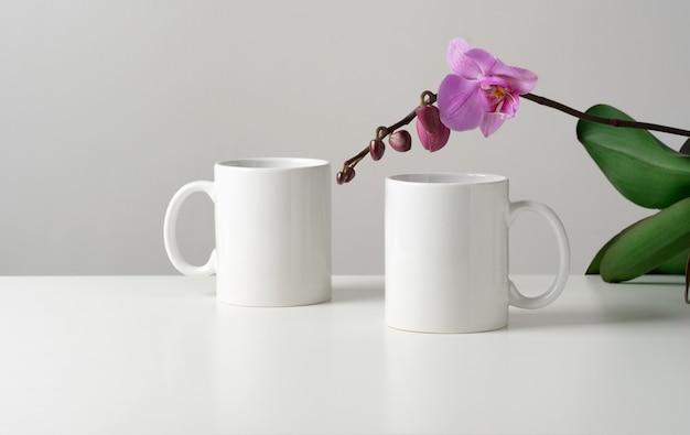 Mockup di due tazze bianche su un tavolo con decorazioni di fiori di orchidea in un interno minimalista.