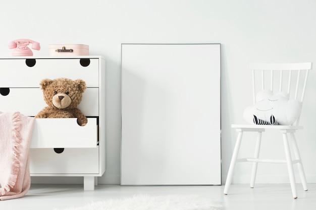 Mockup di poster vuoto bianco tra sedia e armadietto nella foto reale interna della stanza dei bambini