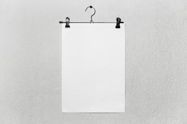 Mockup di carta bianca attaccata al gancio di stoffa sulla superficie strutturata bianca.