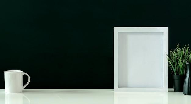 Mockup cornice in legno bianco, tazza e pianta da appartamento su tavolo bianco con sfondo nero, copia spazio.
