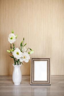 Mockup con photoframe, fiori bianchi eustoma o lisianthus in vaso sulla tavola di legno con lo spazio della copia.