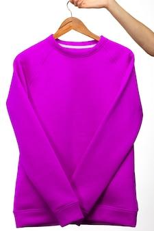 Mockup della mano della donna che tiene maglioni viola su sfondo bianco
