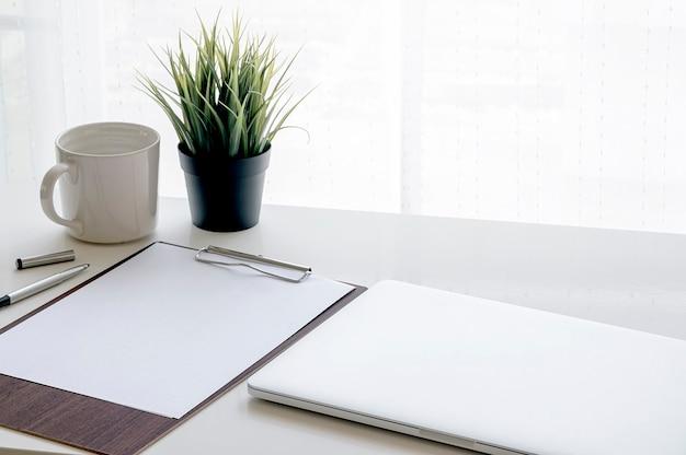 Mockup appunti in legno con carta a4 vuota e laptop sul tavolo bianco in camera moderna.