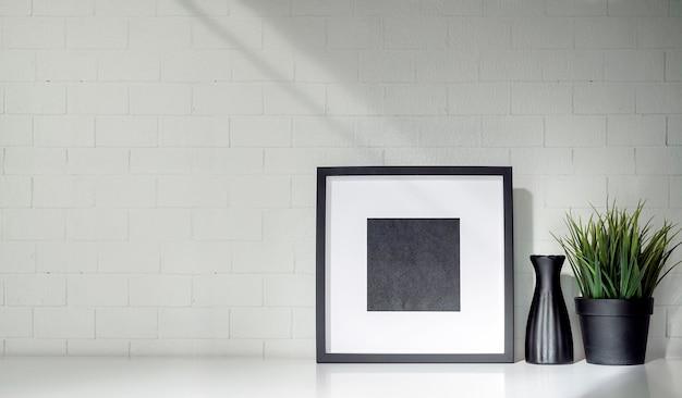 Cornice in legno mockup, vaso in ceramica e pianta d'appartamento sul tavolo con muro di mattoni.