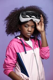 Mod ragazza dai capelli castani ricci vestita con la giacca sportiva rosa che indossa sulla testa gli occhiali per realtà virtuale posa in studio su sfondo al neon.
