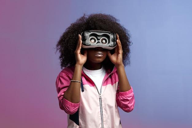 Mod giovane ragazza riccia dai capelli castani vestita con la giacca sportiva rosa utilizza gli occhiali per realtà virtuale in studio su sfondo al neon.