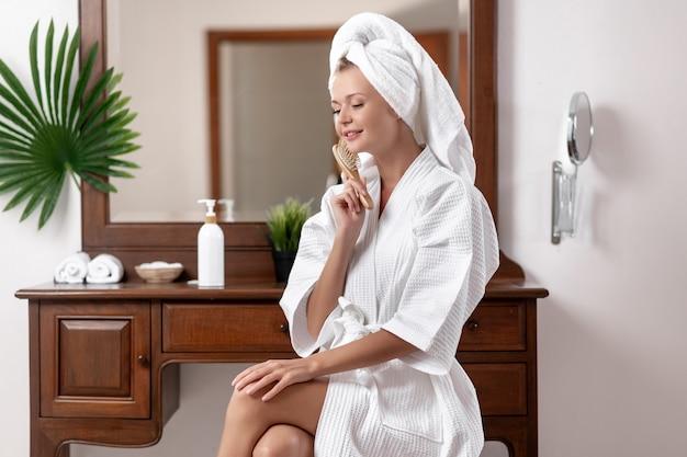 Una modella in accappatoio e asciugamano in testa posa mentre è seduta su una sedia vicino alla toletta