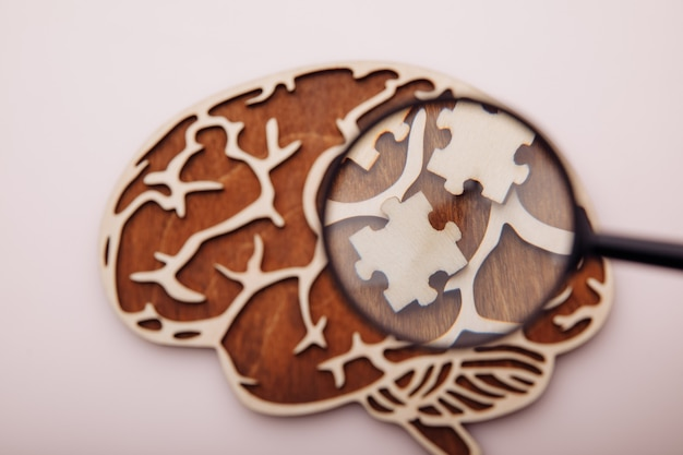 Modello di cervello e puzzle in legno su uno sfondo rosa. salute mentale e problemi con il concetto di memoria.