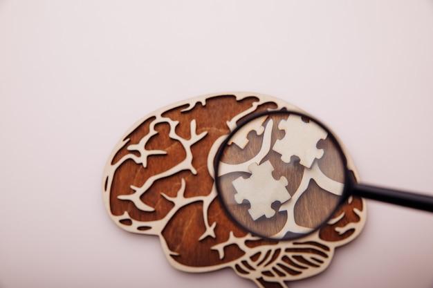 Modello di cervello e puzzle in legno con lente d'ingrandimento, concetto di assistenza sanitaria.