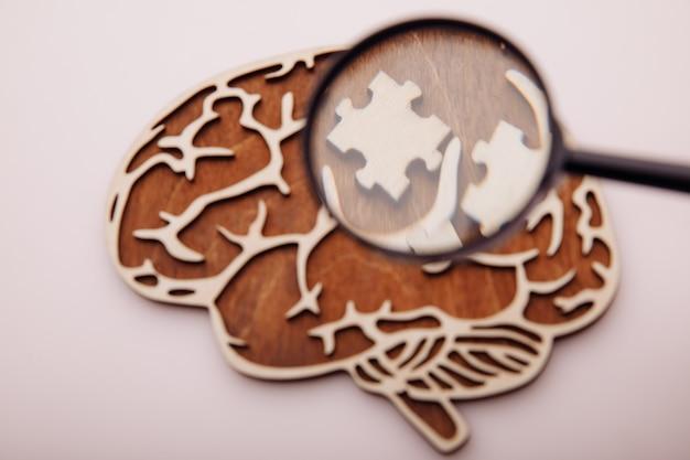 Modello di cervello e puzzle in legno con lente d'ingrandimento, ricerca di soluzioni.