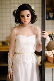 Bruna modello in capelli corti in posa in un abito da sposa bianco