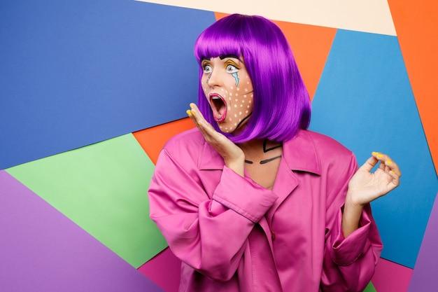 Modello in un'immagine creativa con trucco pop art contro colorato