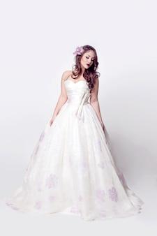 Modello vestito in abito da sposa, con acconciatura e fiore nella sua acconciatura, isolato su bianco