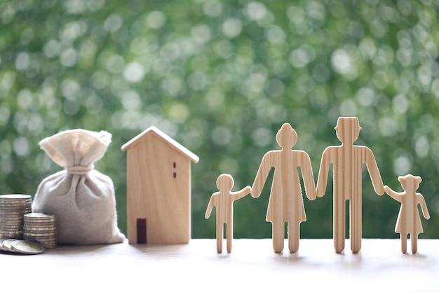 Modello di famiglia e modello di casa con borsa di denaro e pila di monete soldi su sfondo verde naturale