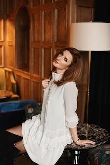 Ragazza di modello nel vestito chiaro che si siede sulla tavola nell'interno di lusso del ristorante