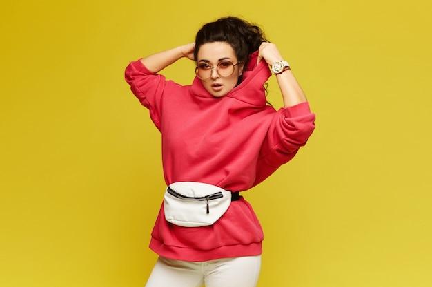 Ragazza modello in jersey rosa, occhiali da sole alla moda e con marsupio isolato su giallo