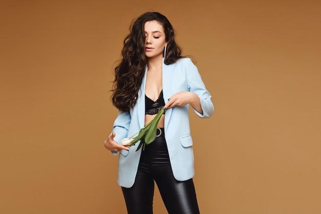 Modello di ragazza con lunghi capelli ricci e perfetto corpo snello mantiene i fiori di tulipano e posa sul muro beige, isolato con copia spazio per testo e pubblicità