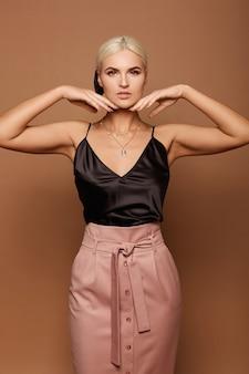 Una ragazza modello con trucco perfetto con la camicetta nera e la gonna beige guardando nella telecamera e in posa sullo sfondo beige