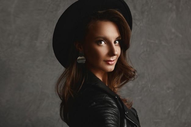 Ragazza di modello con trucco perfetto in cappello alla moda e una giacca di pelle su sfondo grigio