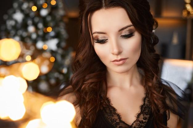 Ragazza modello con acconciatura alla moda in camicetta nera in posa con luci natalizie festive