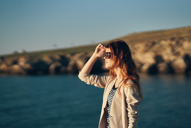 Modello in occhiali donna che cammina sulla spiaggia vicino al mare nella vista laterale del garage garage