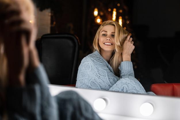 Modello di una giovane donna felice con un sorriso positivo in un elegante abito blu lavorato a maglia sta riposando vicino a uno specchio bianco vintage con lampade luminose in una stanza con un albero di natale