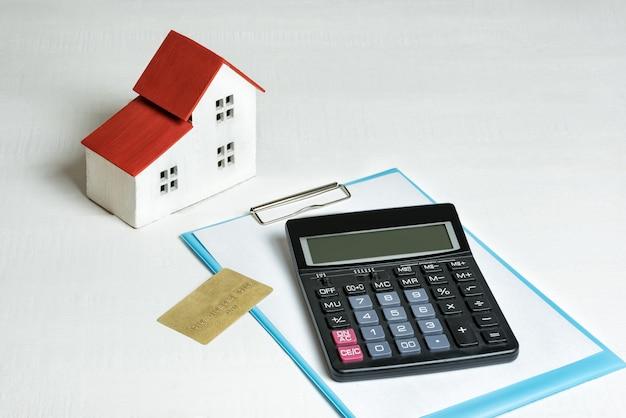 Modello di casa, carta di credito e calcolatrice accesi. comprare una casa. concetto di mutuo e immobiliare.