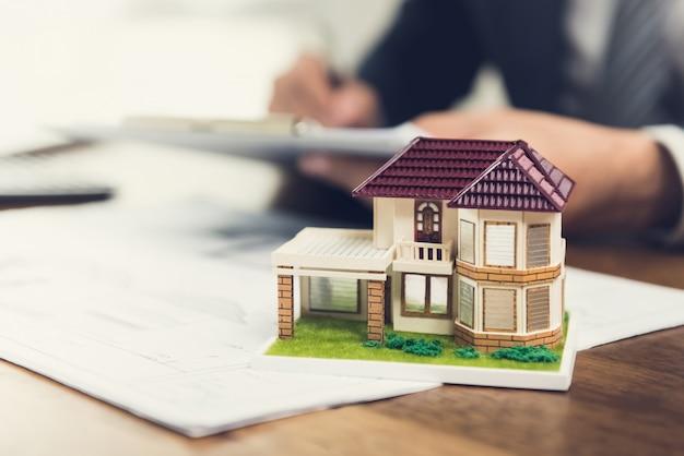 Casa modello su una scrivania con planimetrie per un progetto