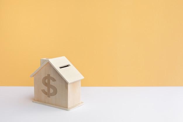 Modello di casa in legno con sfondo color pastello