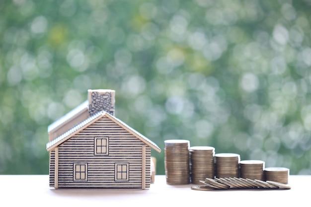 Casa modello e pila di monete denaro su sfondo verde naturale, investimento e concetto di business