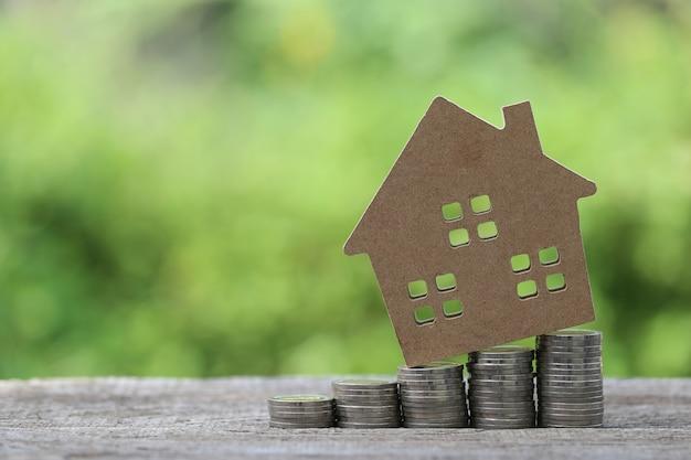 Modello di casa sulla pila di monete soldi su uno spazio verde naturale