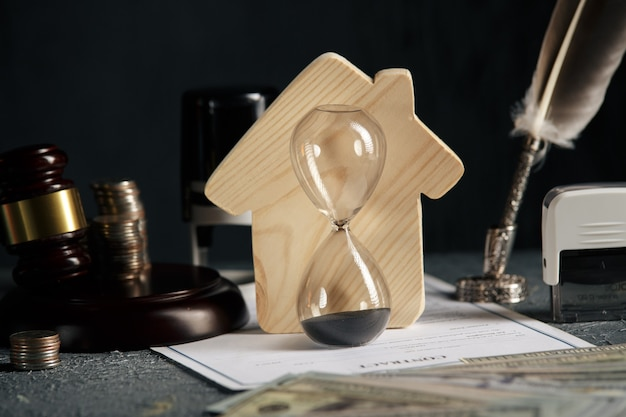 Modello di casa, timbro, martelletto e clessidra sulla scrivania. casa immobiliare e concetto di asta.