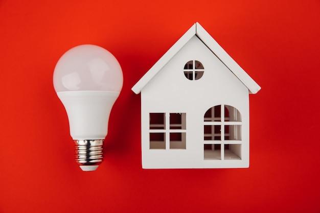 Modello di casa con e lampadina sul tavolo. ecologia del concetto di energia elettrica.